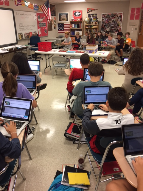 Kids sitting down in a classroom with iPads